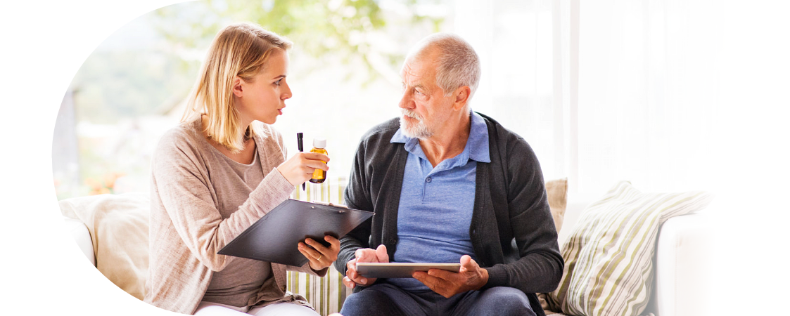 caregiver holding medicine bottle talking to old man