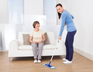 caregiver mopping the floor smiling