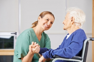 caregiver looking at old woman happily